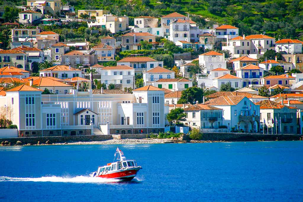 Small red motor boat transfer people to Spetses island, Greece