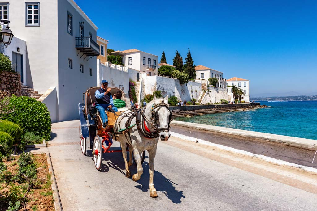 A young couple enjoys a ride by the seaside, with a horse carriage in Spetses near Athens